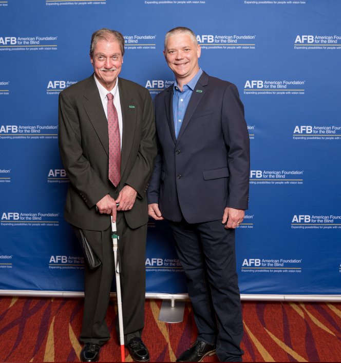 Group Photo:  From the HPE Product Accessibility Program Office, Bill Tipton wearing a charcoal grey suit with white shirt and mauve tie  and Bill Bettega, wearing a navy suit with royal blue shirt.