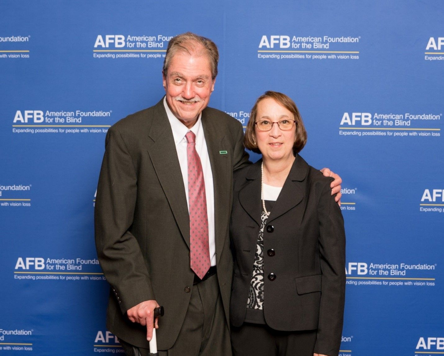 Group Photo:  Bill Tipton, from the HPE  Product Accessibility Program Office with his wife Kathy.  Bill is wearing a  charcoal grey suit with white shirt and mauve tie and Kathy is wearing a black pantsuit with a black and white lace top.