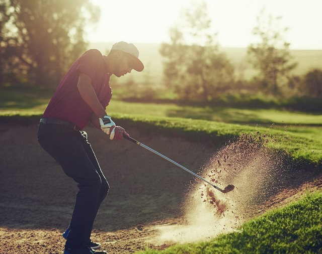 Golfer hitting out of sand trap