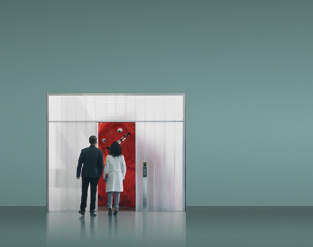 Man and woman looking through doorway at I.T. monster