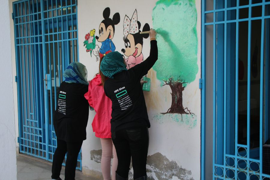 HPE employees painting an outdoor area at a Children's Hospital