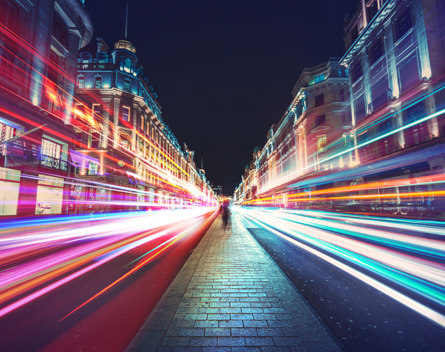 Street at night with headlights in motion