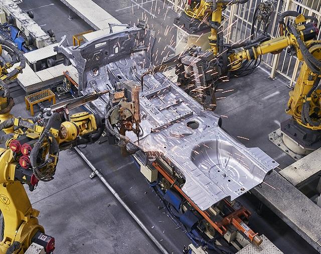 Robotic welders working on automobile frame