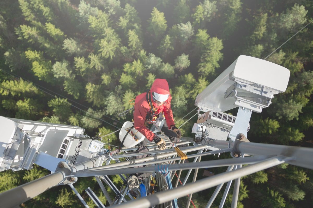 Engineer climbing a 5G Open RAN cellular tower