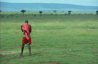 A member of the Masai tribe uses mobile technology In the Masai Mara National Reserve in Kenya, Africa.