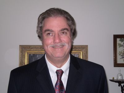 Above is a photo of Bill Tipton standing smiling wearing a dark    charcoal grey suit with a white dress shirt and red and blue  paisley tie.