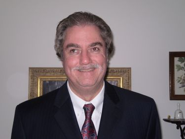 Photo of Bill Tipton standing smiling wearing a dark charcoal grey suit with a white dress shirt and red and blue paisley tie.JPG